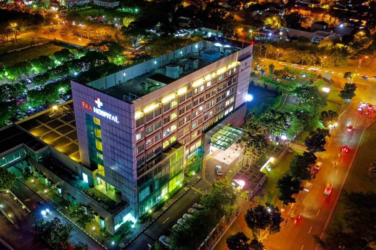 hospital beside vehicle park and road at night